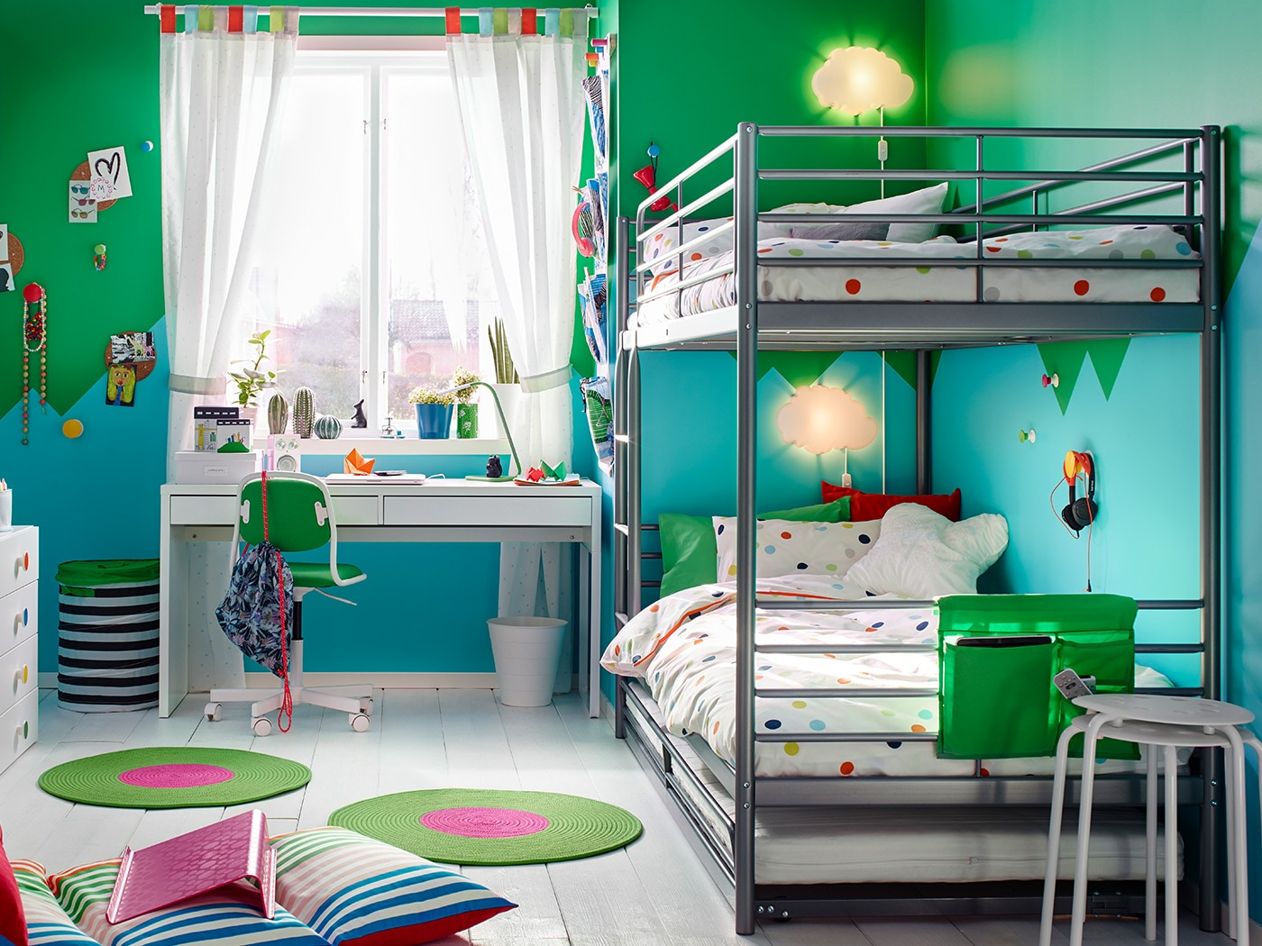 A SVÄRTA bunk bed frames with printed duvets and a white desk in a children's bedroom.