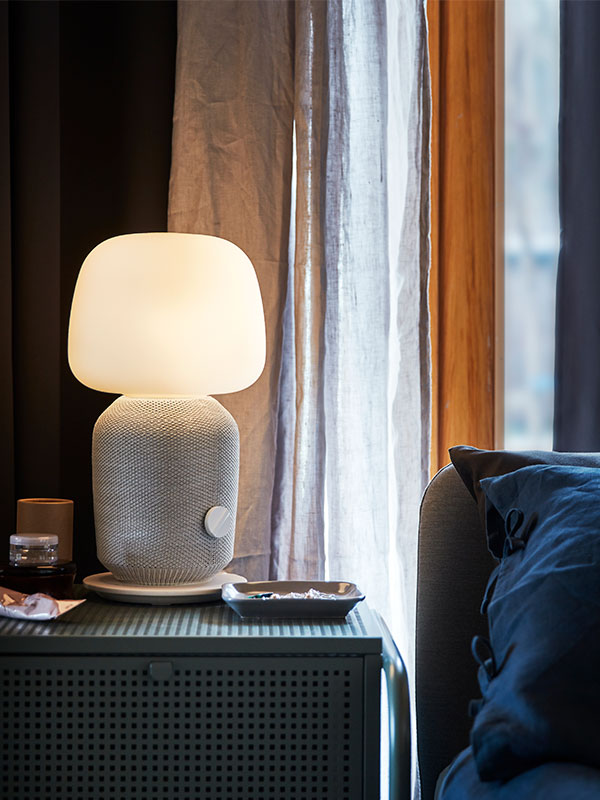 A SYMFONISK table lamp on a nightstand next to a bed