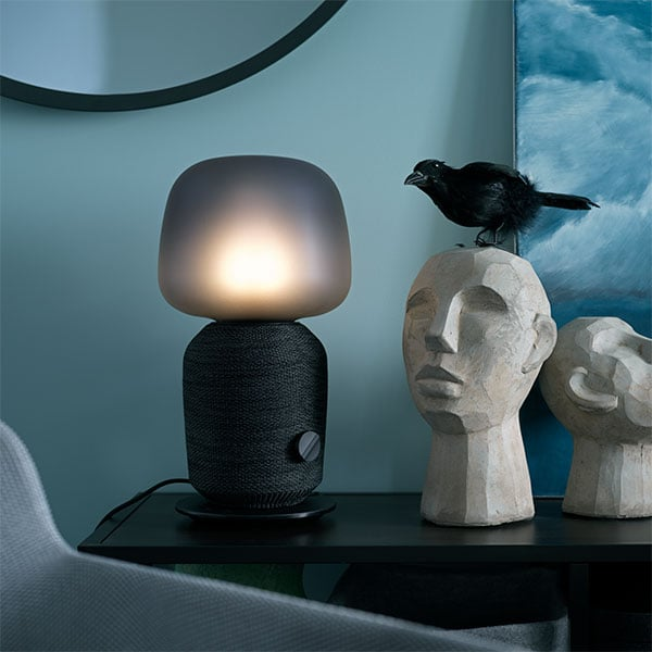 A SYMFONISK table lamp on a nightstand next to a bed. A black bird is sitting on top of a sculpture next to the lamp.