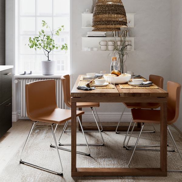 A table in brown-stained oak veneer, four chairs in golden-brown leather, a pendant lamp in seagrass and a beige rug.