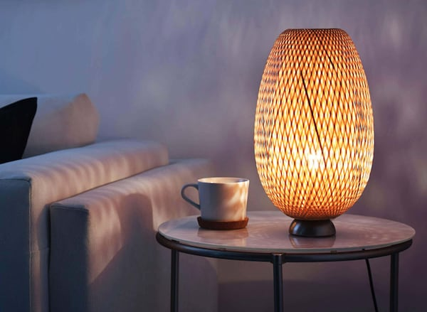 A table lamp and coffee mug on a living room side table