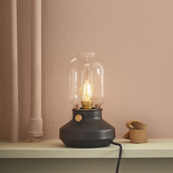 A table lamp that looks like an oil lamp on a shelf.