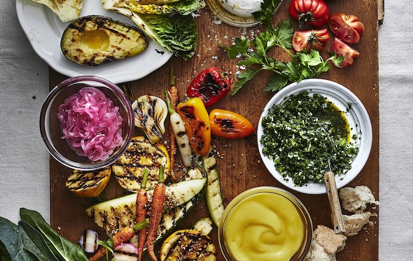 A table of colorful grilled vegetables and herbs.