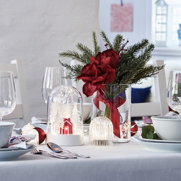 A table prepped for Christmas with STRÅLA LED table decorative lighting, VINTERFEST dishes and an artificial flower bouquet.