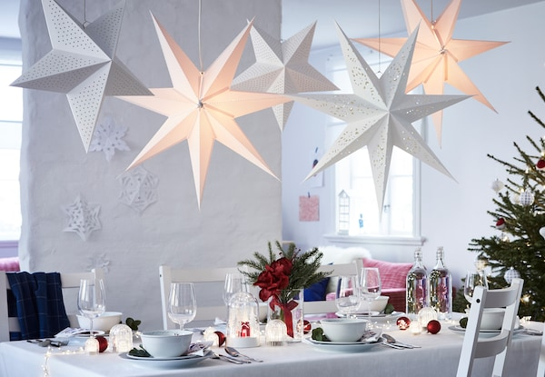 A table prepped for Christmas with STRÅLA lighting and VINTERFEST tableware.