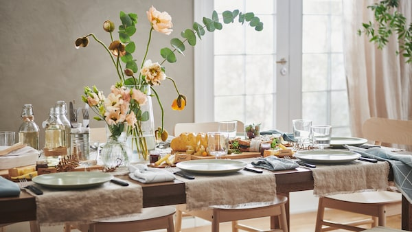 A table set for a meal with neutral tones and light green tableware. A vase of flowers, food and bottles are on the table.