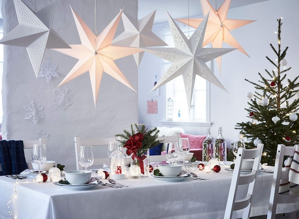 A table set for dining with festive holiday decoration, white chairs, and paper star lanterns hanging above.