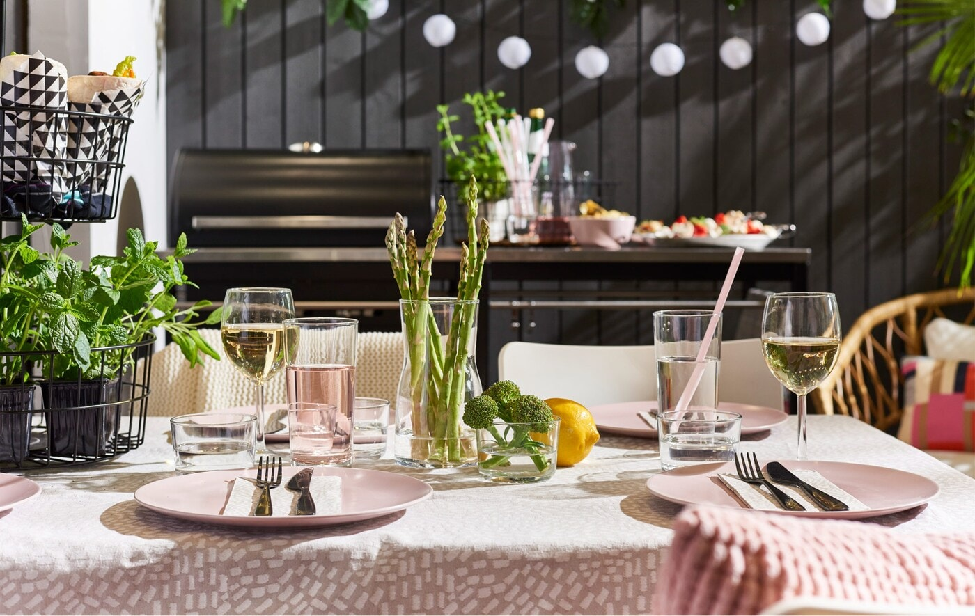 A table set for lunch outside, in front of a barbeque area, with a SOLVINDEN lighting chain in the background.
