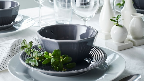 A table set with grey and white dishes and touches of greenery.