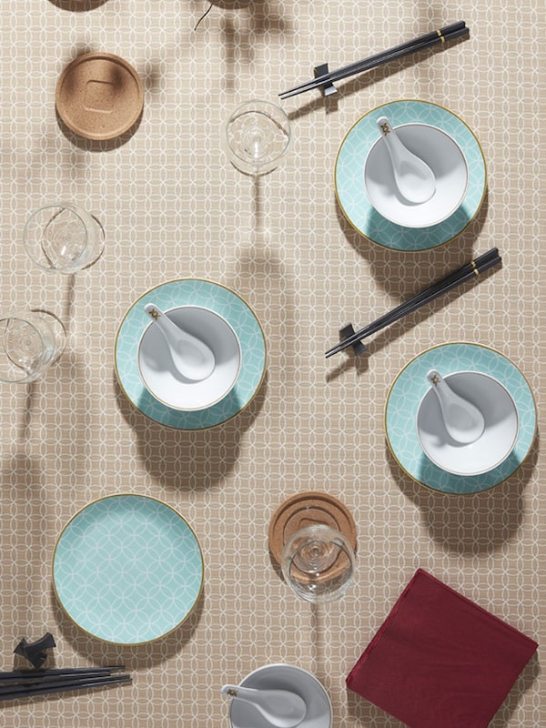 A table set with light blue dinnerware, a beige tablecloth and red napkins