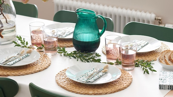 A table set with round placemats, white dishes, and a green jug.
