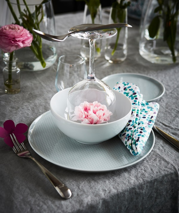 A table setting with a KRUSTAD light grey plate, an upturned glass in a bowl and a colourful napkin.