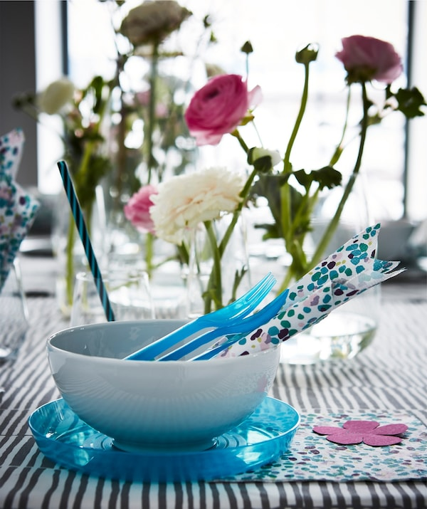A table setting with blue and white dinnerware with multicoloured paper napkins and flowers.