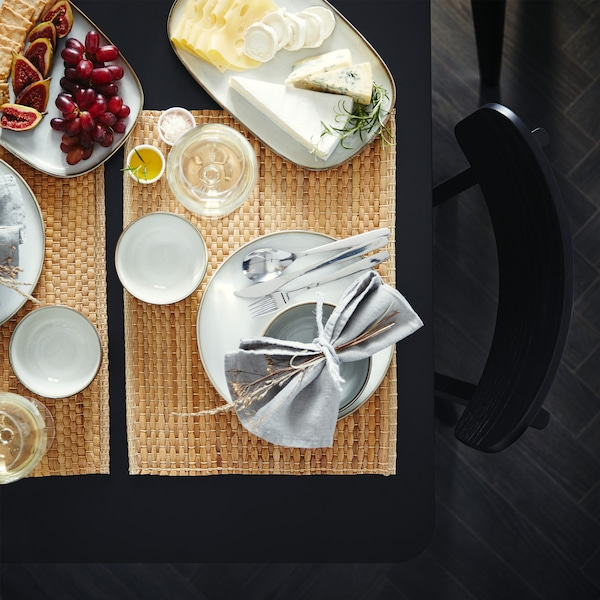 A table that's set with place mats made from water hyacinth, grey dinnerware and two serving plates with cheese and grapes.