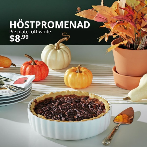 A table top with the HÖSTPROMENAD pie dish filled with a pie, pumpkins and autumn leaves sit in the background.
