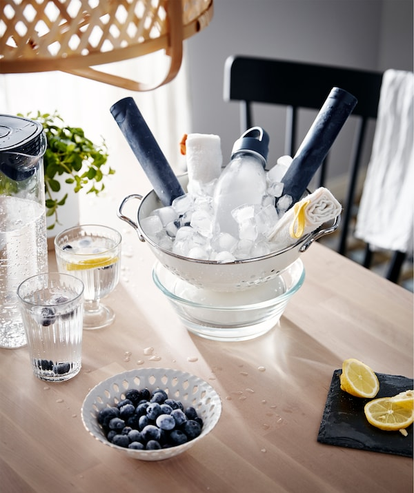 A table with different cooling agents, such as iced water jug in glasses and an ice-filled colander placed in a bowl.