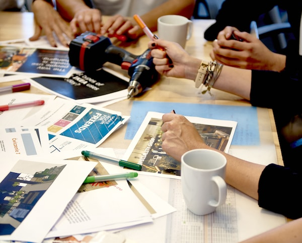 A table with papers fanned out, a drill, a white coffee mug and several arms leaning on the table.