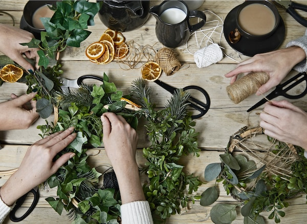 A table with three pairs of hands making festive wreaths.