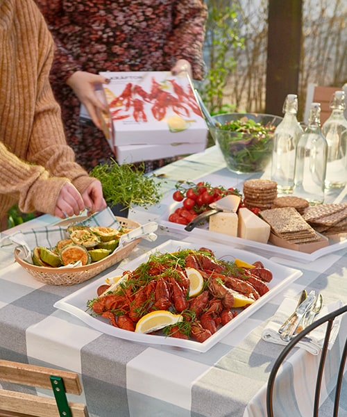 A tablescape outdoors in the summer with a plate of crayfish and crackers with cheeses.