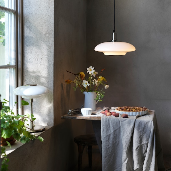 A TÄLLBYN table lamp is on a windowsill, while a TÄLLBYN pendant lamp hangs over a table with a pie and flowers on it.