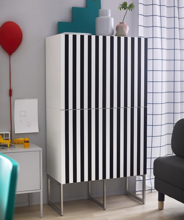 A tall cupboard with striped black and white front.