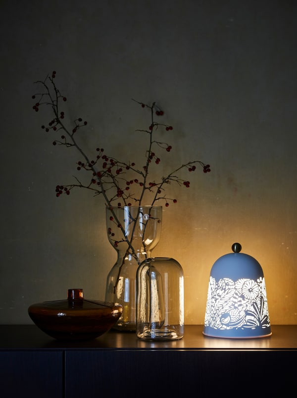 A tall decorative vase with autumn foliage and two short vases and a nature-inspired lamp set on a sideboard.