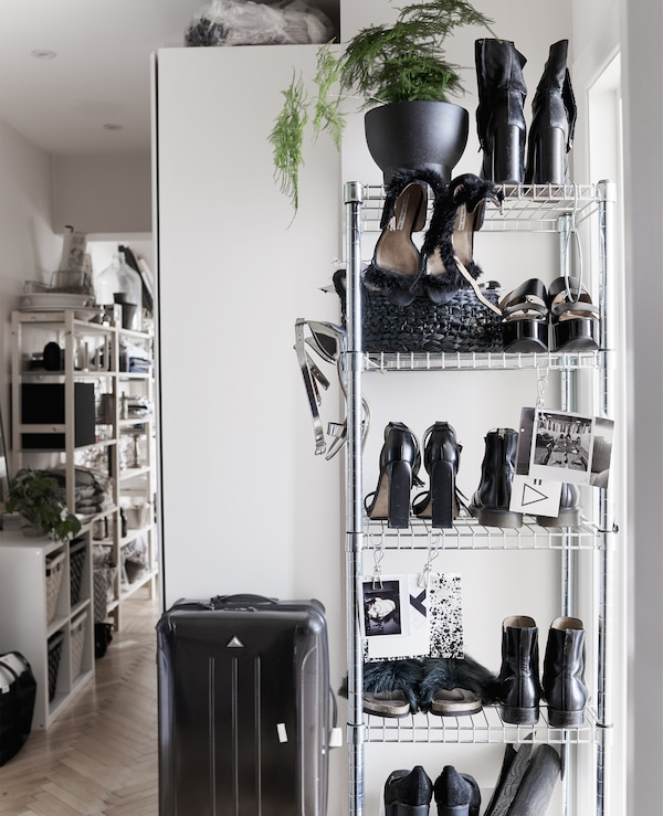 A tall open-storage shelving unit filled with shoes and a black suitcase.