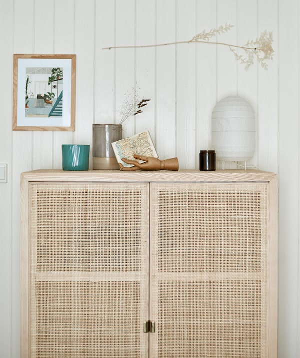 A tall wooden storage cabinet with woven doors set against a panelled wall with a paper lantern and objects displayed on top.
