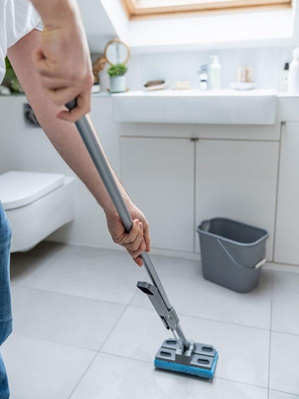 A TaskRabbit Tasker mopping a bathroom floor.