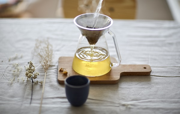 A tea strainer over a glass pot, on a wooden chopping board.