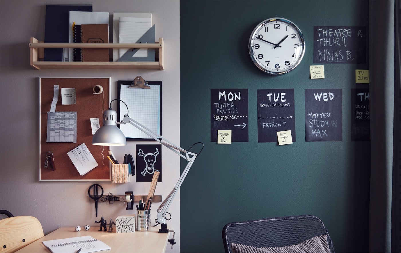 A teen room study area with a desk, work lamp, shelves, clipboard, clock, noticeboard and weekly planner on the wall.