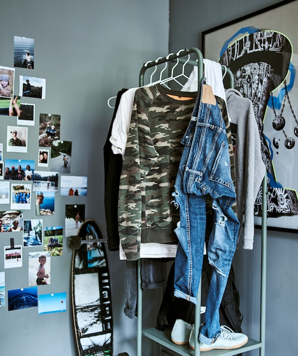 A teen room with grey walls, industrial style clothes storage, graffiti artwork and a skateboard leaning on the wall.