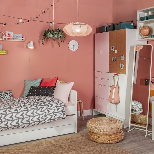 A teen's bedroom with painted walls has a wardrobe, standing mirror, footstools, and an extendable bed that comes with storage.