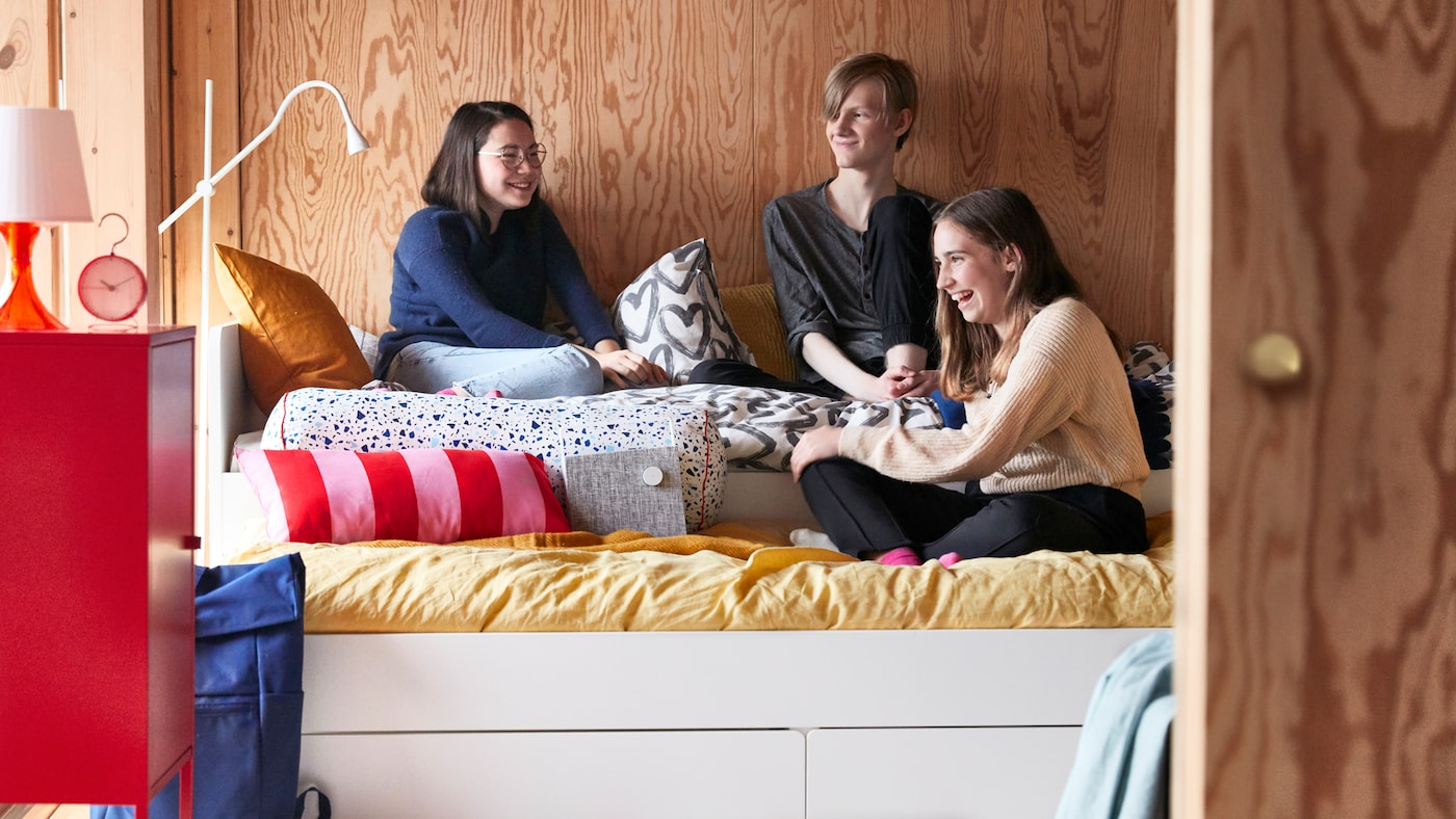 A teen's room with a white SLÄKT bed frame, cushions and quilt covers in different colours, and three friends hanging out.