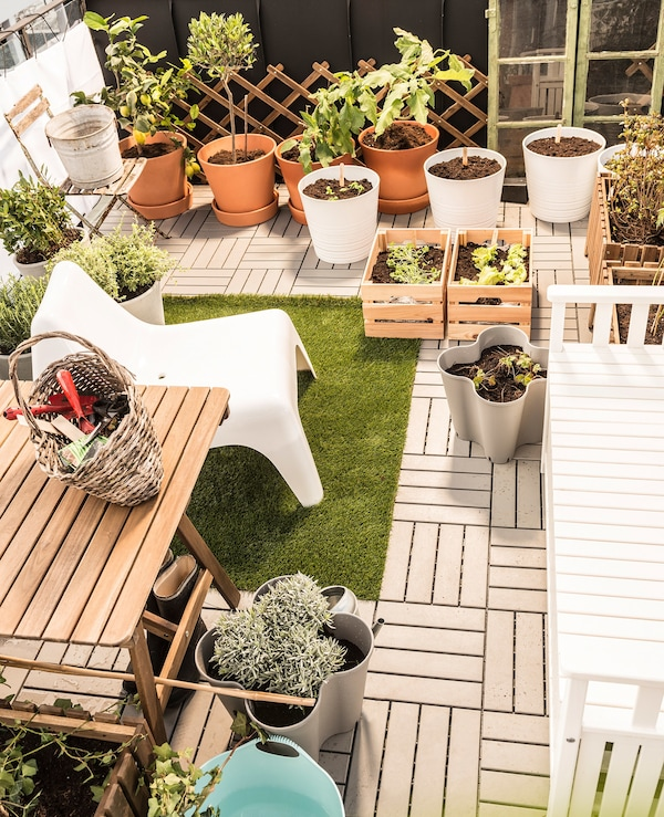 A terrace with white garden chair, plant pots and decking.