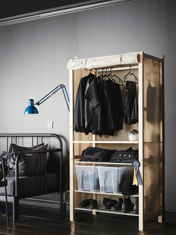 A textile sheath turns an IVAR shelving unit standing in a minimalistic, grey room, into a wardrobe, filled with clothing.