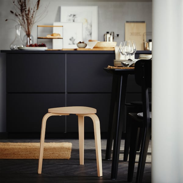 A three-legged stool in birch, a black cabinet with decorative items on the top surface and a table and two chairs in black.