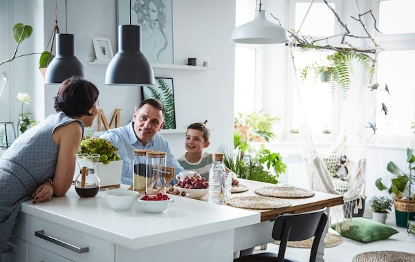 A three-person family around the kitchen island in a large, bright, white kitchen with lots of plants and green accents.