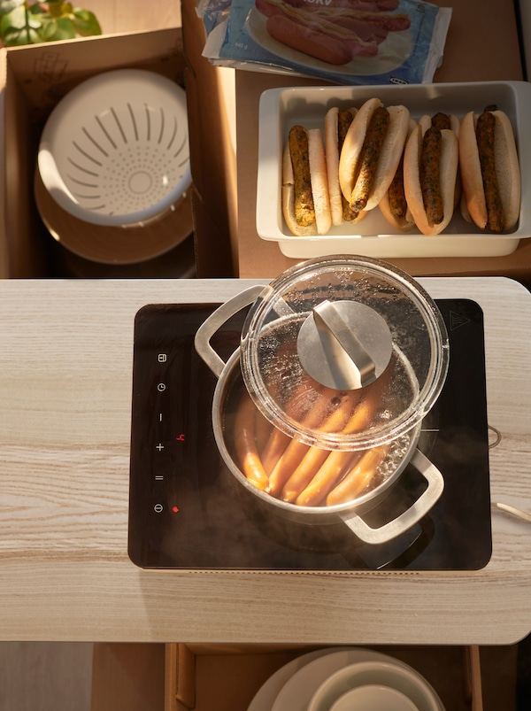 A TILLREDA induction hob with a batch of simmering hot dogs, next to it trays of vegetarian and meat sausages in bread.