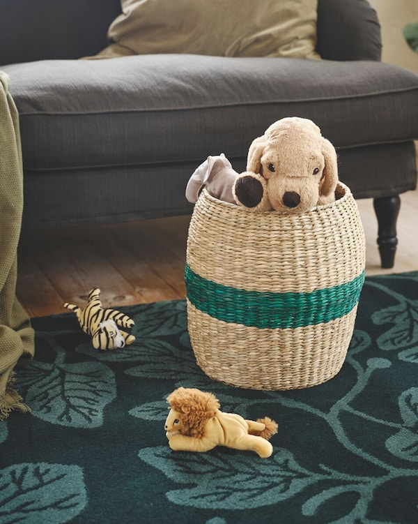 A TJILLEVIPS basket with a green stripe through the middle sitting on a green rug with stuffed animals inside and around it.
