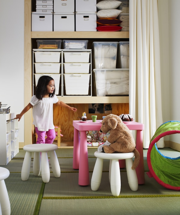 A toddler having a tea party with a soft toy, open storage in the background.