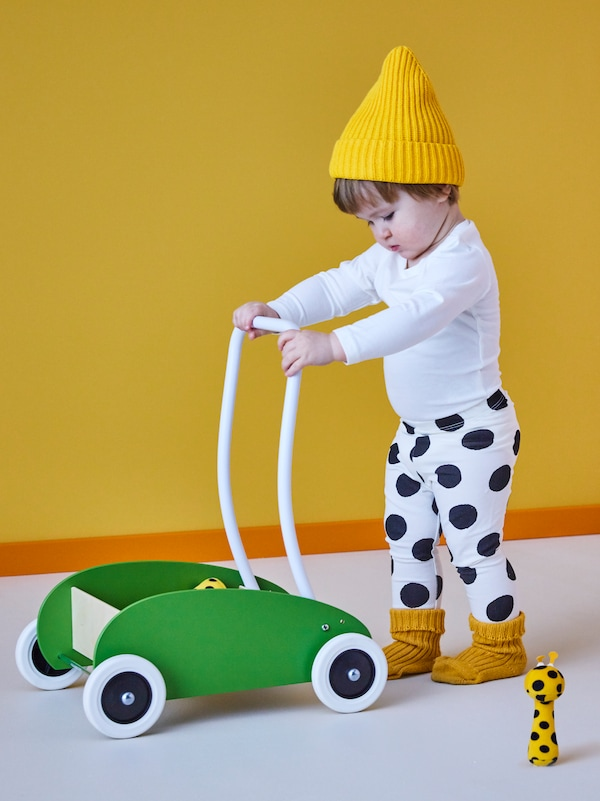 A toddler pushing a wooden trolley, a KLAPPA rattle can also be seen.