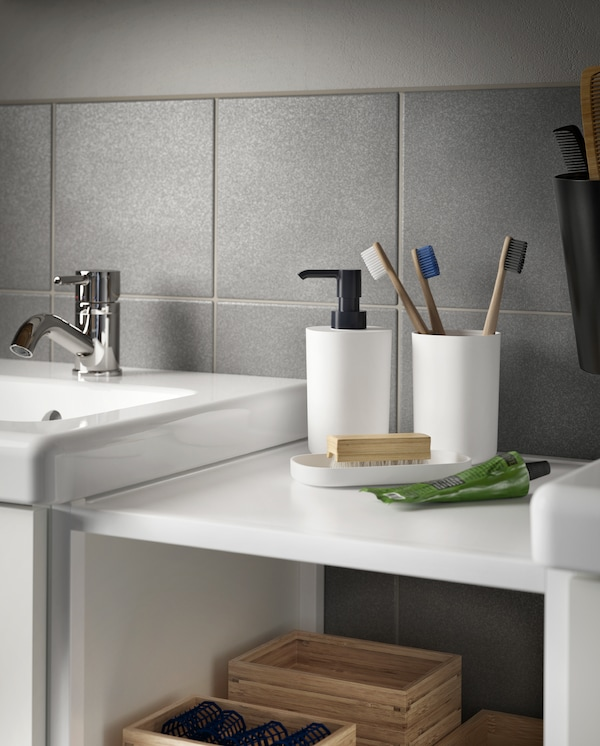 A toothbrush holder with three toothbrushes, a soap dispenser and a tray in black/white stand on a shelf beside a wash-basin.