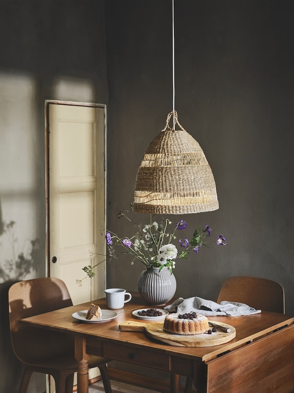 A TORARED pendant lamp hangs over a wooden dining table with cake, coffee and a vase of flowers on it.