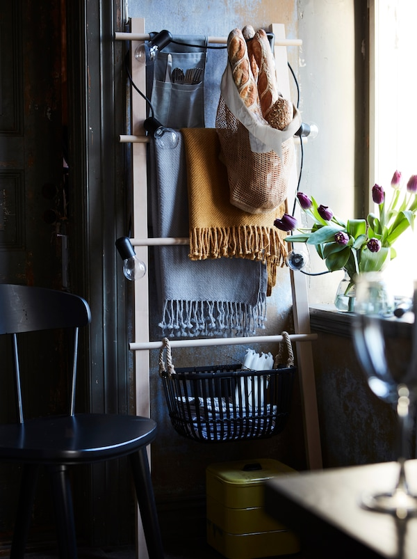 A towel stand is propped against a wall and used as extra storage. Throw blankets and baskets hang from it.