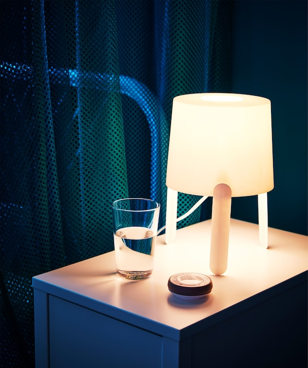 A TRÅDFRI remote control dimmer on a bedside table with a lamp.