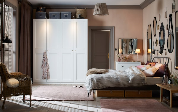 A traditional bedroom in soft pink and light grey with two white wardrobes next to each other.