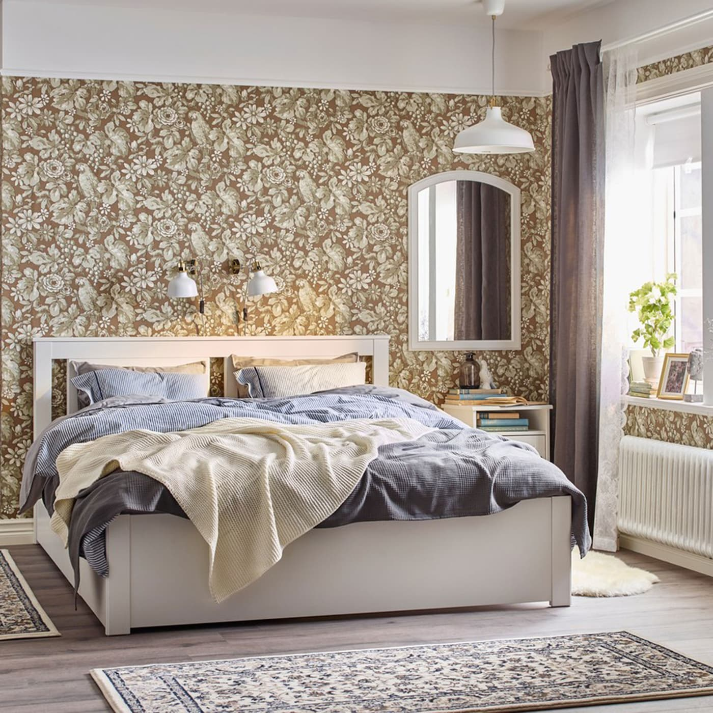 A traditional beige, blue and white bedroom with a white IKEA SONGESAND bed and frame, bedside table and chest-of-drawers.