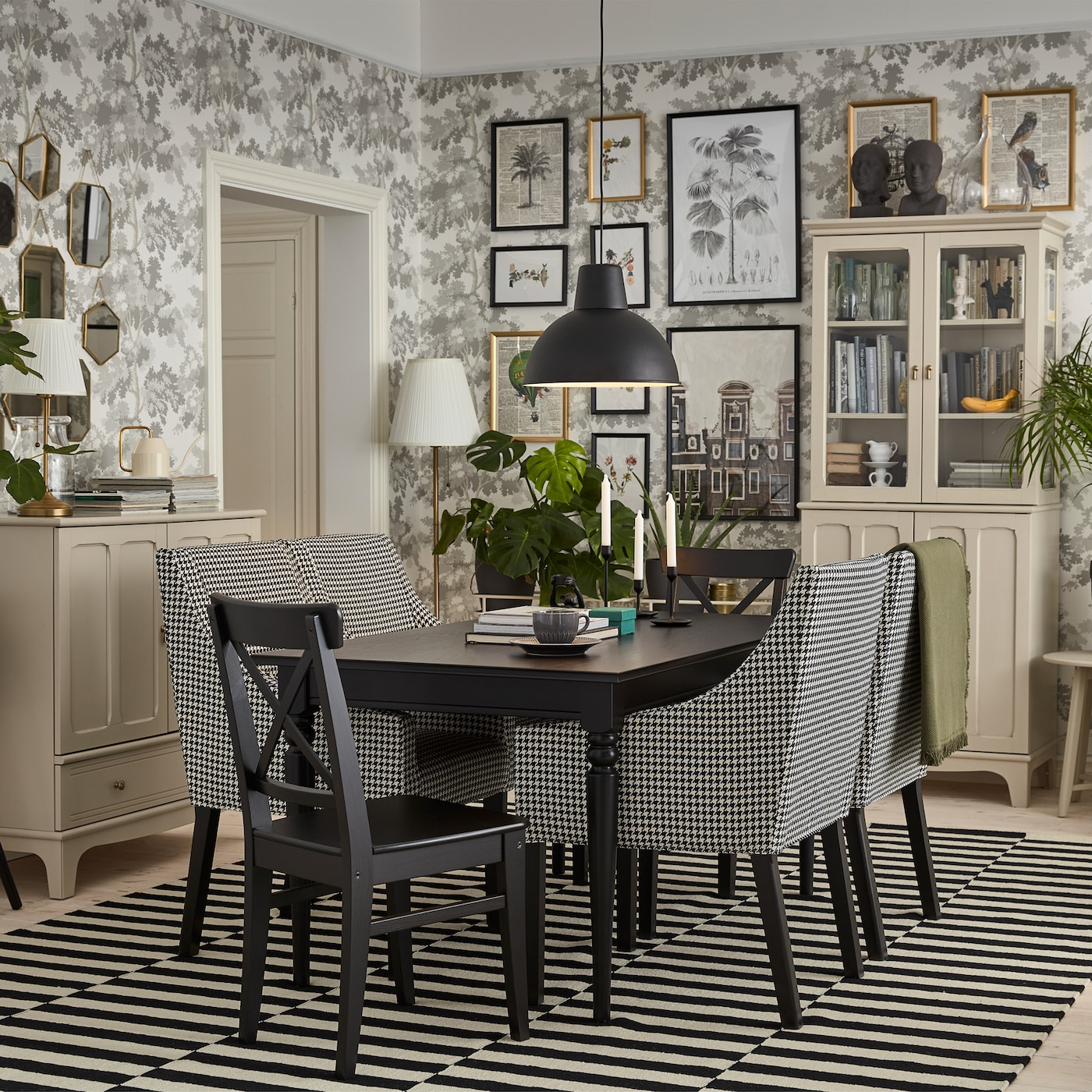 A traditional dining room with a black table, light beige cabinets, black/white chairs with armrests and a striped rug.