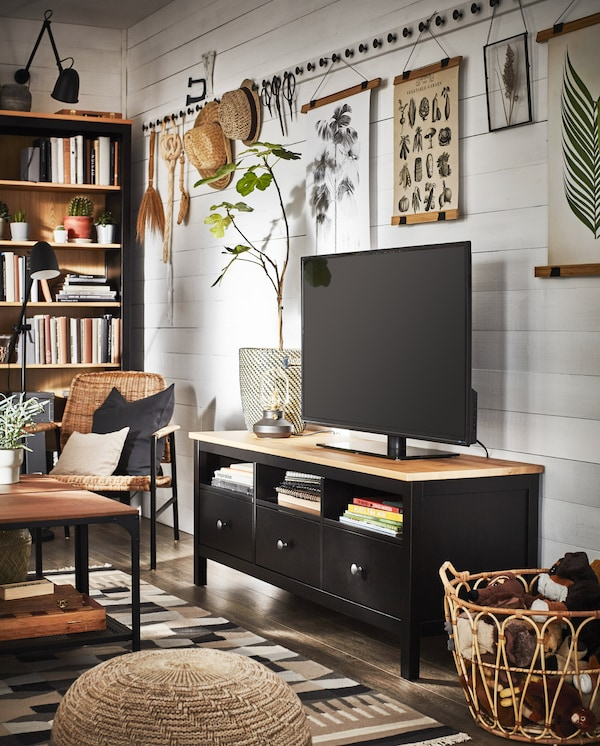 A traditional living room with a TV bench and a bookcase in black-brown/solid pine and decorative items in natural materials.